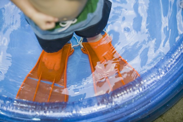 Boy wearing flippers in kiddie pool