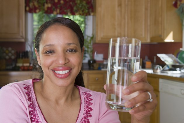Hispanic woman holding a glass of water and smiling