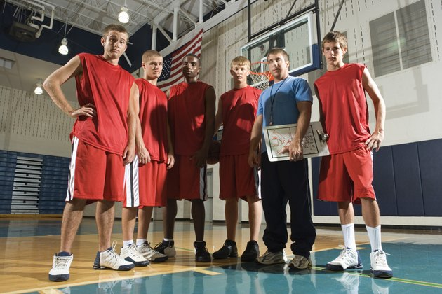 Basketball team and coach posing in gym