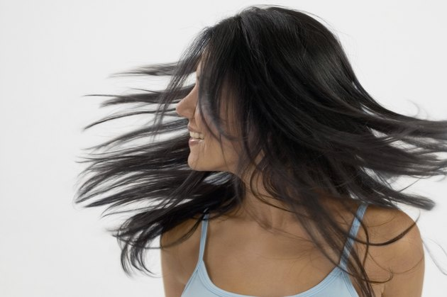 Young woman turning her head so that hair is in her face