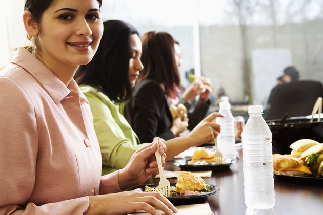 Female office workers sitting, eating