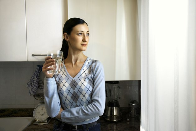 Woman holding glass of water in kitchen
