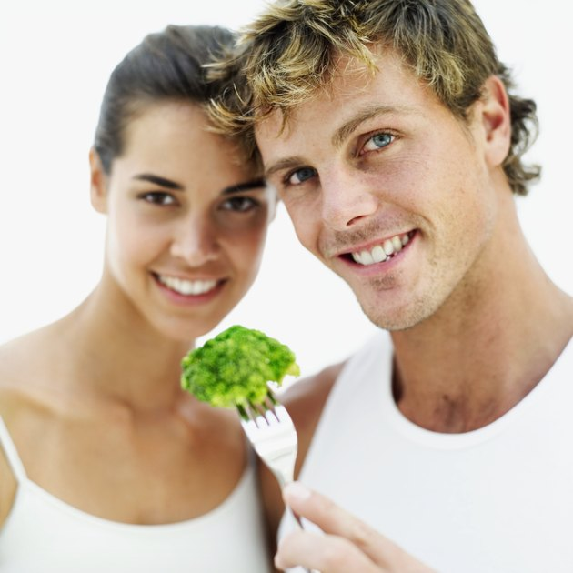 young couple holding a piece of broccoli on a fork