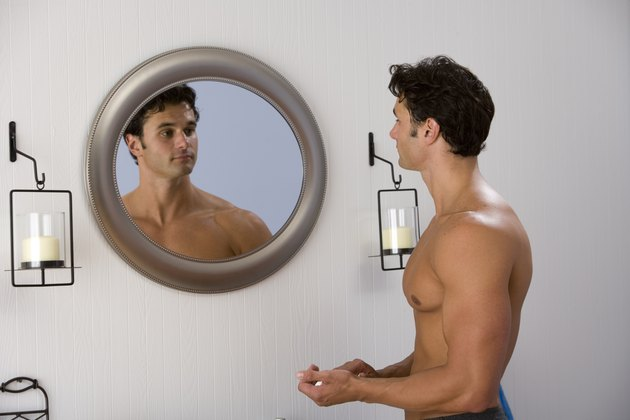 Muscular man looking at reflection in mirror