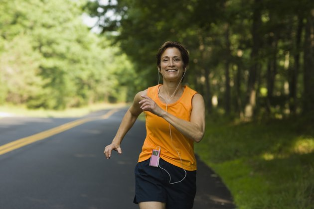 Smiling woman jogging along road