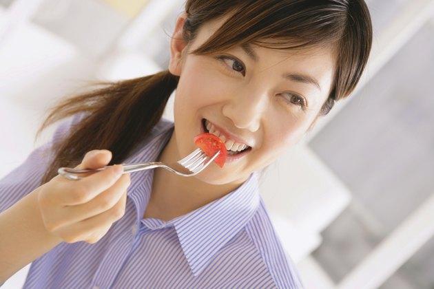 Young Woman Eating Tomato