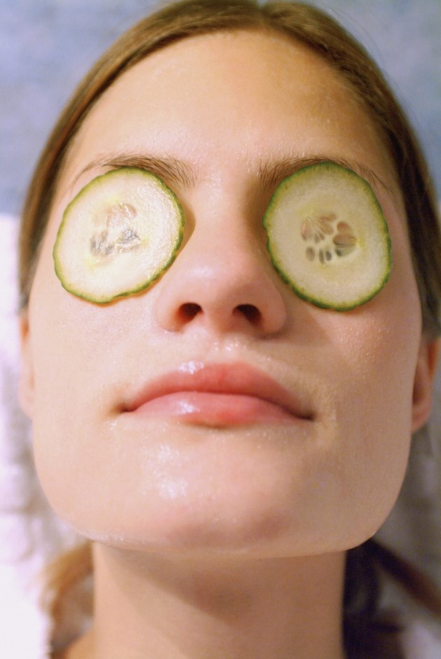 Close-up of a mid adult woman with cucumber slices on her eyes