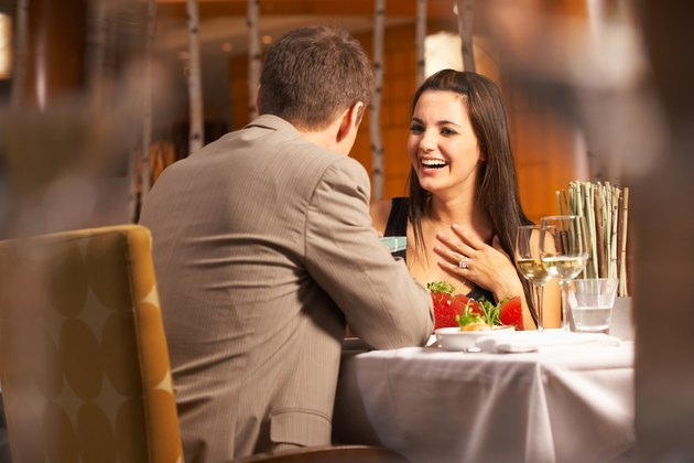 Woman receiving gift from man in restaurant