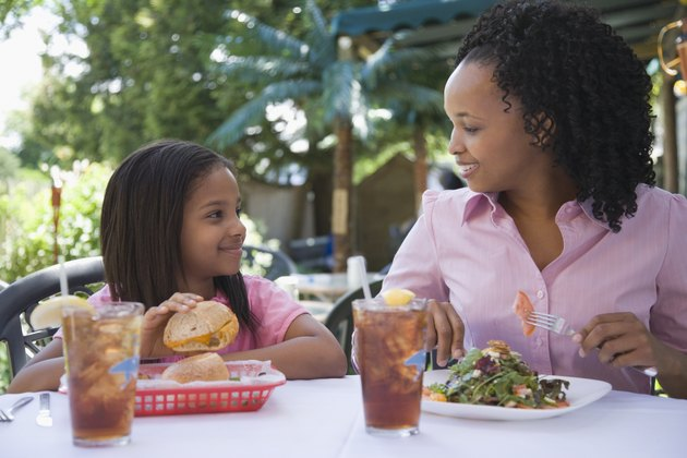 Mid adult woman with her daughter sitting at the breakfast table and smiling