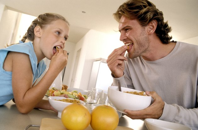 Father and daughter eating cereal