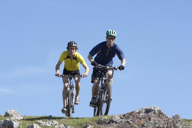 Two men riding mountain bikes on rocky ground