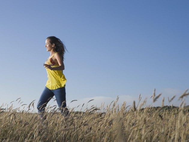 Hispanic woman walking in field