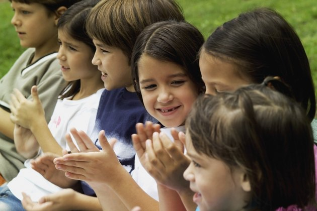 Six children outside clapping hands, close-up