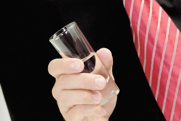 Mid section view of a man holding a shot glass of tequila