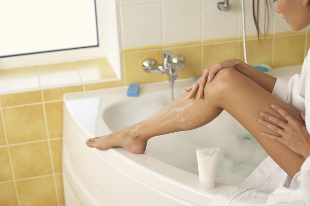 Woman sitting on side of bathtub and putting lotion on her legs
