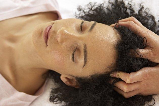 Therapist massaging woman's scalp