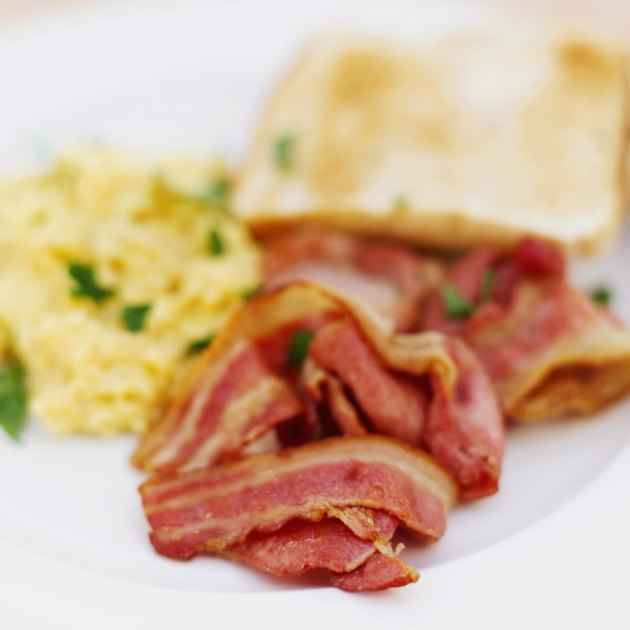 close-up of bacon served with scrambled eggs and toast
