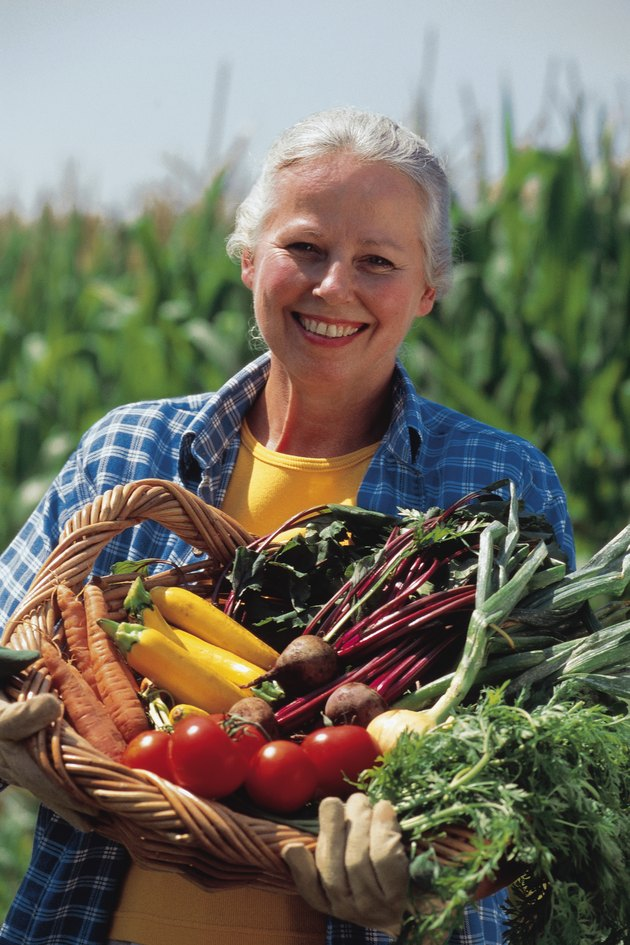 Mature woman holding a basket of fresh vegetables
