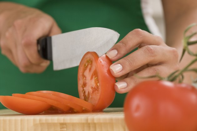 Woman slicing tomatoes with knife