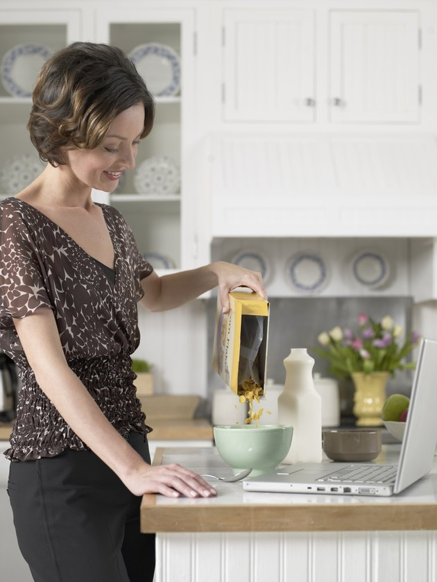 Mid adult woman pouring breakfast cereals