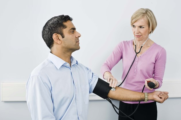 Doctor checking blood pressure on patient