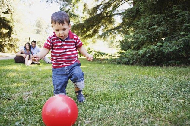 Toddler boy kicking red ball