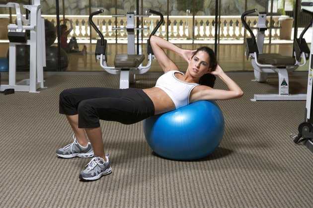 Woman doing exercise on fitness ball in gym, side view