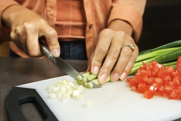 Hands of woman slicing vegetables
