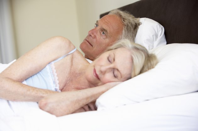 Senior Woman In Bed With Worried Husband