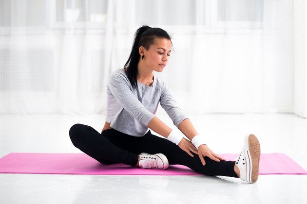 Fit woman doing aerobics gymnastics stretching exercises her leg and