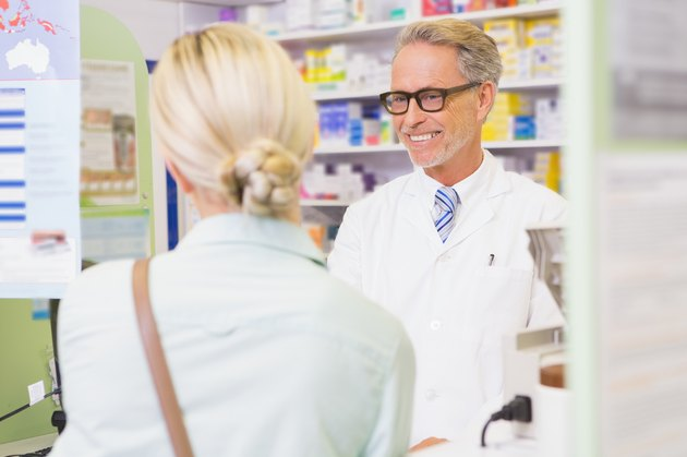 Senior pharmacist speaking with customer
