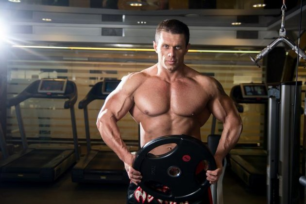 Handsome muscular man in the gym. Bodybuilder with the disc. Muscle training, fitness