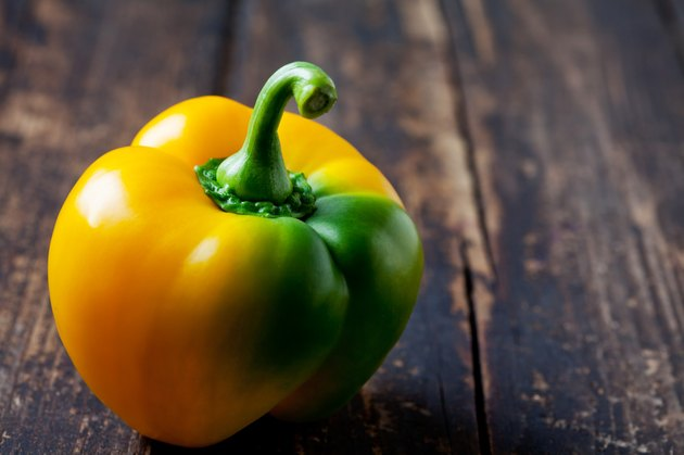 Yellow green pepper on wood