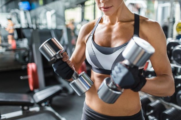 Female athlete with barbells exercising in gym