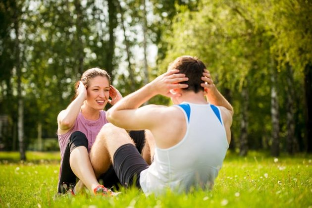 Sport couple making sit-ups together in nature on green grass