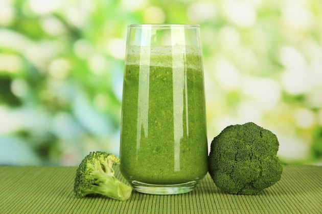 Glass of broccoli juice, on bamboo mat,  green background