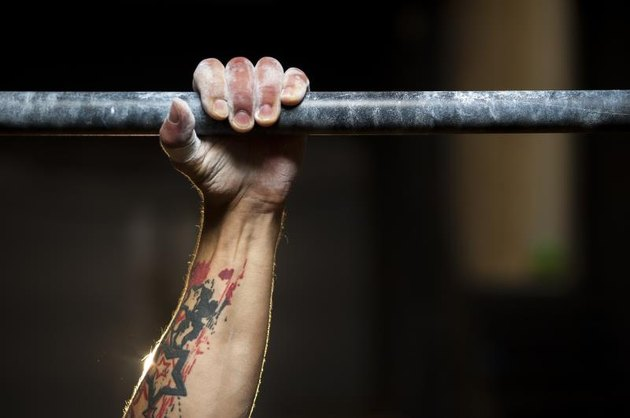 Closeup of male hand in horizontal bar. Pull ups exercise