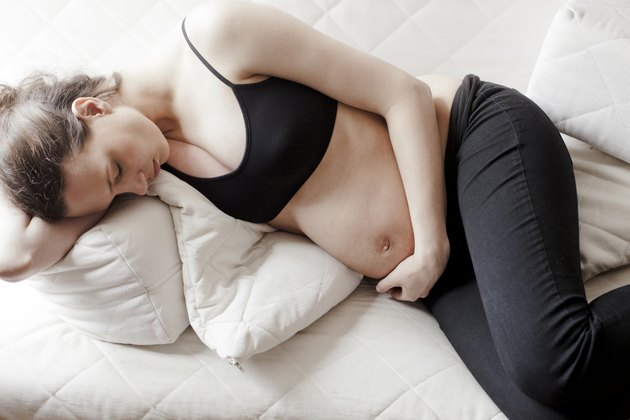 Pregnant girl resting on sofa, holding her tummy