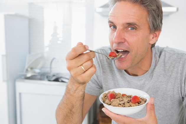 Happy man eating cereal for breakfast in kitchen