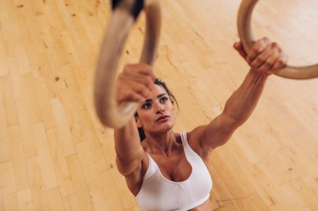 Determined young woman at gym. Muscular female athlete working out using gymnastic rings.