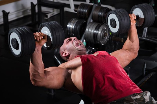 Muscular men exercising with weights. He is performing dumbbell bench press for chest muscles.