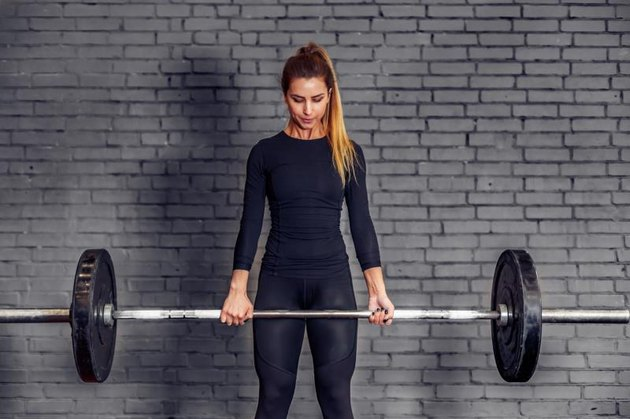 Young sports woman with weight barbell doing deadlift exercise. Fit female athlete in great shape is lifting weights in a sport gym. Athletic woman train gym workout.