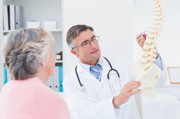 Doctor explaning anatomical spine to senior woman