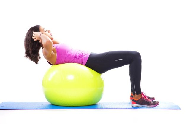 Woman doing abdominals with a fitness ball