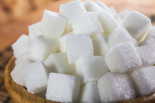Pile of Sugar Cubes over Wooden Background