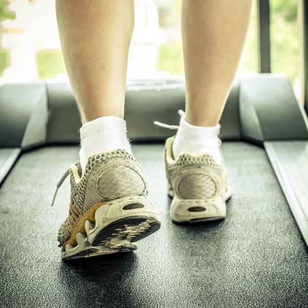woman's muscular legs on treadmill