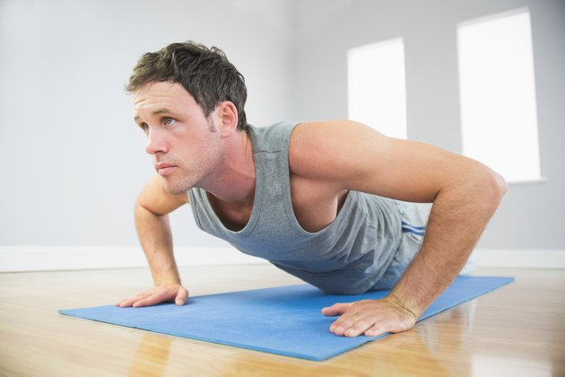 Attractive sporty man doing push ups on blue mat