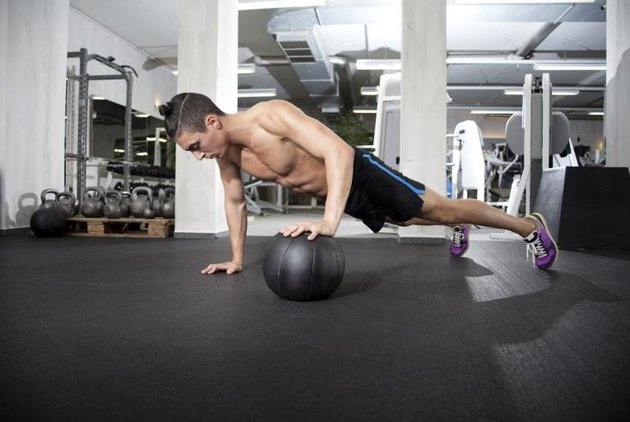 Fit and attractive athlete is performing a one-handed push-up in a medicine ball.