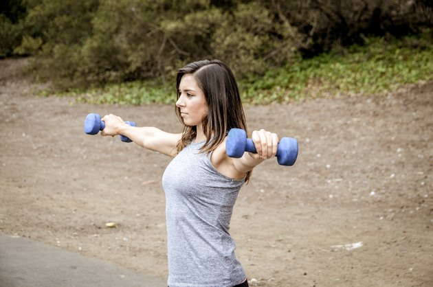 Athletic woman lifting dumbbells in park