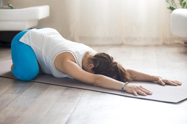 Healthy lifestyle concept. Pregnancy Yoga and Fitness. Young pregnant yoga woman working out in living room interior. Pregnant fitness model lying in Prenatal Balasana, Child Pose after practice